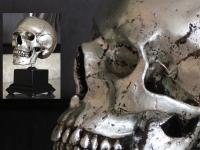 Human skull in silver pewter on pedestal